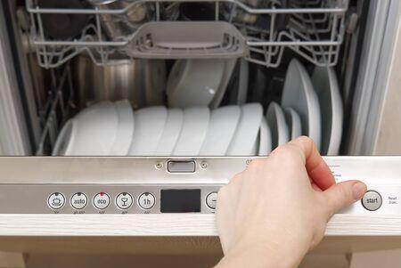 Full loaded Dishwasher machine. Dishwasher with white plates front vew 版權商用圖片