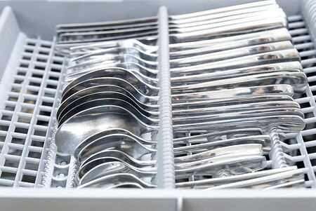 Clean cutlery is in the dishwasher. close - up