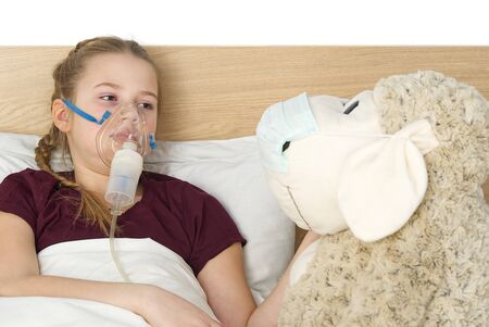 girl with inhaler mask - respiratory problems for asthma. girl with a mask inhaler lies with a toy in bed and breathes adrenaline. health care and sick child concept