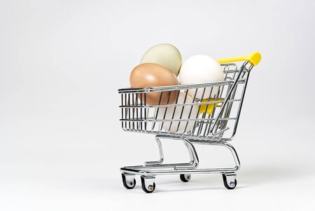 chicken colored eggs in a shopping cart isolated on white. isolated on white