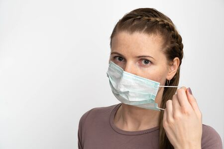 adult woman puts a protective mask on her mouth to protect herself from viral diseases and bacteria. surgical mask protects against coronavirus Reklamní fotografie