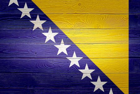 Bosnia and Herzegovina flag painted on old wood plank background. Brushed natural light wooden texture. Wooden texture flag of Bosnia and Herzegovina.