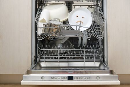 Poorly washed dishes in the dishwasher. Integrated Dishwasher with white plates front vew and sad emotion on plate. broken dishwasher machine concept Reklamní fotografie
