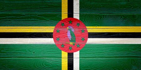Dominica flag painted on old wood plank background. Brushed natural light knotted wooden board texture. Wooden texture background flag of Dominica.