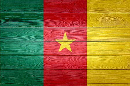 Cameroon flag painted on old wood plank background. Brushed natural light knotted wooden board texture. Wooden texture background flag of Cameroon.
