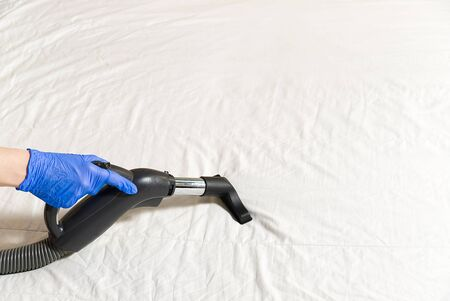 Vacuuming bed. Domestic home cleaning concept. Textile sofa chemical cleaning. Upholstered furniture. Early spring cleaning or regular clean up. Cleaning Service conceptatHome, apartments, hotels