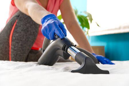 Bed stofzuigen. Huishoudelijk schoonmaakconcept. Textiel bank chemische reiniging. Gestoffeerde meubels. Vroege voorjaarsschoonmaak of regelmatige schoonmaak. Schoonmaak Service concept bij Home, appartementen, hotels. Stockfoto