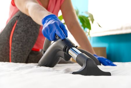 Vacuuming bed. Domestic home cleaning concept. Textile sofa chemical cleaning. Upholstered furniture. Early spring cleaning or regular clean up. Cleaning Service conceptatHome, apartments, hotels. Фото со стока
