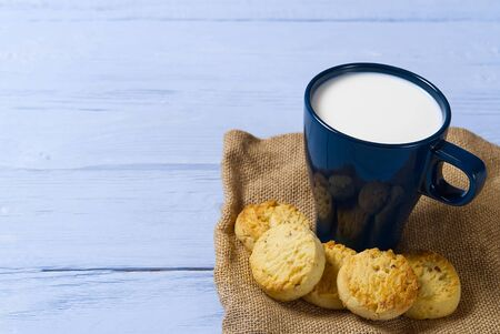 mug of warm milk and cookies before bed. Blue cup with fresh milk and tasty cookies Фото со стока