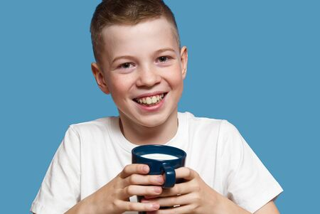Happy Boy with blue mug of Milk Isolated on blue Background. Smiling boy holding blue cup with milk. portrait.