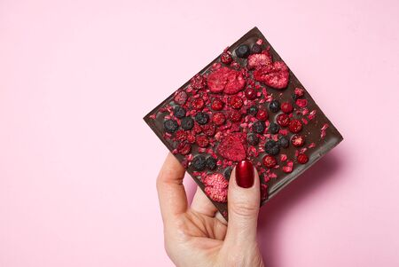 hand holding homemade chocolate with berries on pink background.