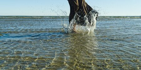 nice legs of a pretty girl walking in water. woman legs, walking on the beach. Legs of a beautiful young girl who runs towards the ocean. Water splashes out