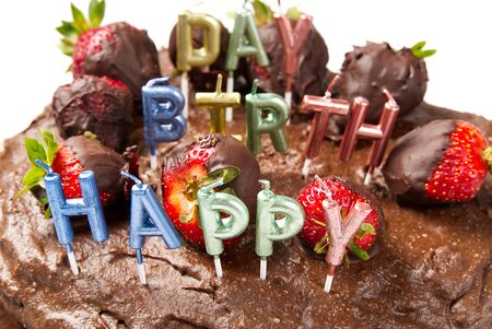 homemade chocolate cake with strawberries and happy birthday candles, close-up. Banco de Imagens