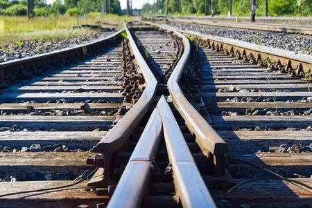 Primer plano del ferrocarril. Vías férreas, hierro tren oxidado detalle ferroviario sobre piedras oscuras.