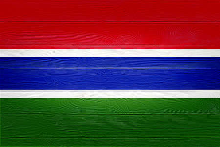 Gambia flag painted on old wood plank background. Brushed wooden board texture. Wooden texture background flag of Gambia.