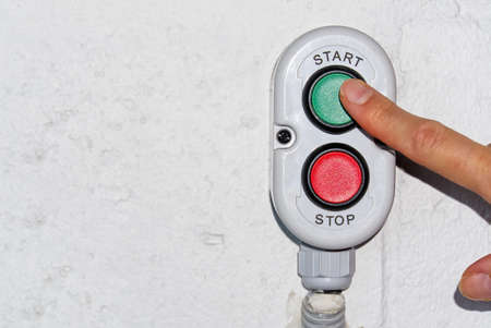 A finger pushing a green start stop button on production.