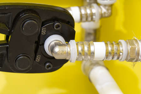 Worker connecting alupex pipes with a tap. Hand press for water pipes PEX - AL - PE-X. plumbing industry. Archivio Fotografico