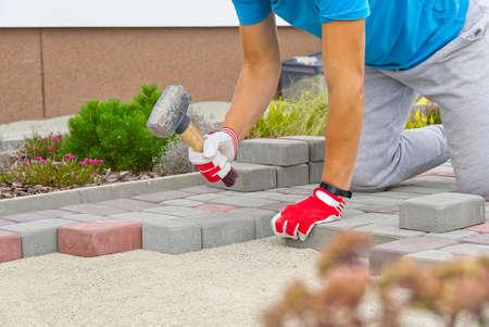 worker laying paving stones. stone pavement, construction worker laying cobblestone rocks on sand. Standard-Bild