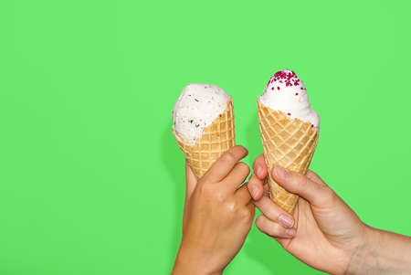 mother and daughter Hands holds ice cream corn with milk ice cream. isolated on a green background.
