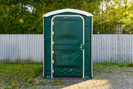 A Green Portable Plastic Toilet in a Park for events.