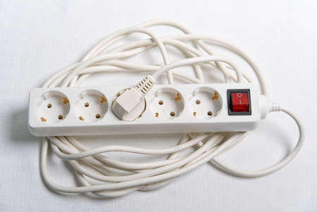 european household white extension cord for 220v with fuse on white textile. close-up