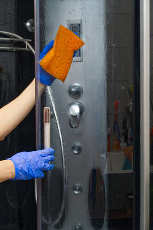 Cleaning of shower steam cabins from calcium deposits. Cleaning in the bathroom. hand in gloves with rag and detergent washing shower and glass