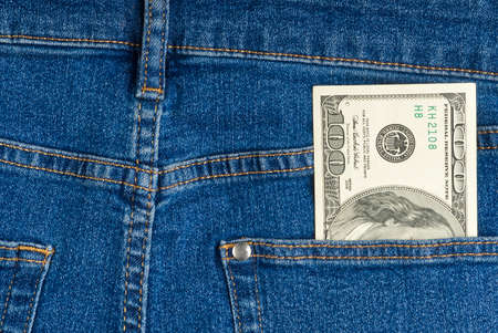 one hundred dollar note in the back pocket of blue jeans. dollar bills in jeans pocket