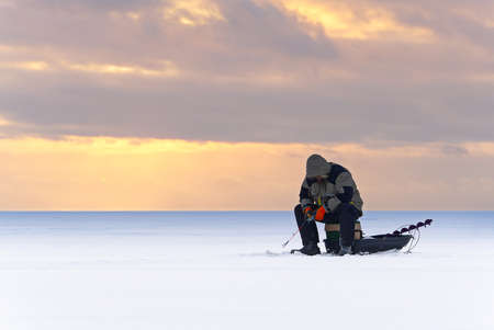 Lonely fisherman at winter fishing. Ice fishing in the north of Scandinavia sunset