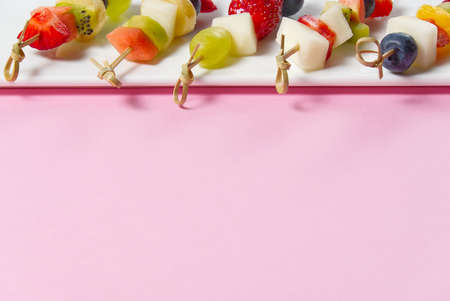 fresh summer fruit snacks on bamboo skewers, isolated on pink