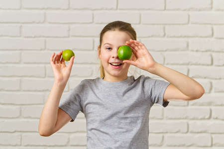 happy girl having fun and covering her eyes with lime , healthy eating, organic food, fruit diet, concept