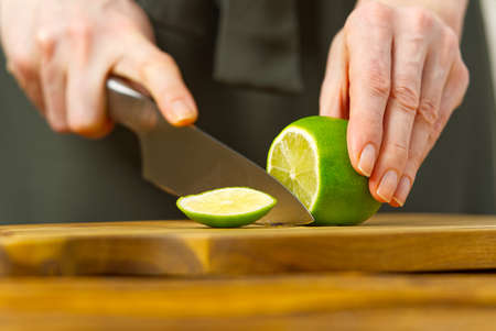 Woman cutting lime in kitchen, lemon water, Refreshing Water with lime and lemon, healthy eating concept