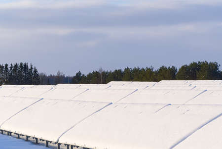 Solar panel field covered with snow. renewable energy in winter low efficiency. renewable green energy industry concept in winter time.