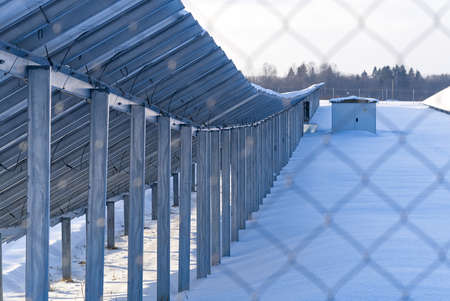 Solar panel back side field covered with snow. renewable energy in winter low efficiency. renewable green energy industry concept in winter time.