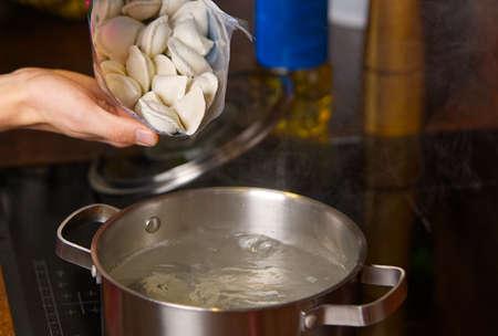 pouring dumplings from the packaging into pots of boiling water. Boiled dumplings in a pan Фото со стока