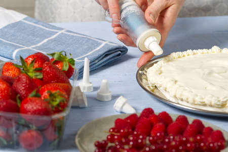woman baker squeezes out whipped cream. Homemade strawberries cake made from meringue cake and cream with strawberries. Фото со стока