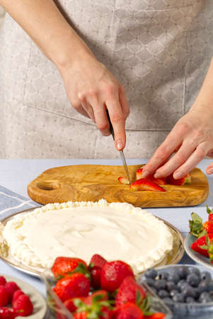woman baker cuts strawberries for strawberry cake. Homemade strawberries cake made from meringue cake and cream with strawberries. Фото со стока
