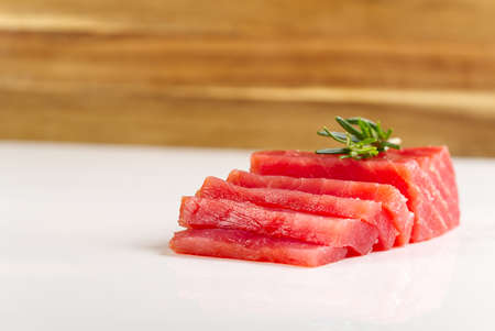 tuna sashimi. fresh yellowfin sliced tuna steak a white table. bluefin tuna medallions