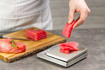 tuna sashimi. Chef weighs the chopped yellowfin tuna. bluefin tuna medallions Фото со стока