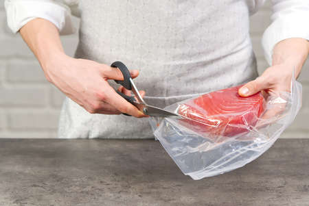 Chef unpack a bluefin tuna steak packed in a vacuum bag