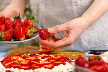 woman baker stacks strawberries on meringue strawberry cake base. Homemade strawberries cake made from meringue cake and cream with strawberries. Фото со стока