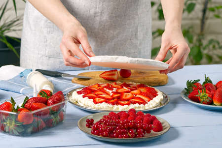 woman baker add a new layer of meringue base in strawberry cake. Homemade strawberries cake made from meringue cake and cream with strawberries.