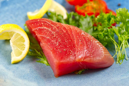 Raw tuna steak with salad and lemon on blue plate. Фото со стока