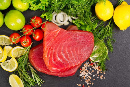 Tuna raw Steak, tuna sashimi, tuna fish sliced with vegetables. healthy eating with seafood, we cook at home. fish meat layout on black stone Фото со стока