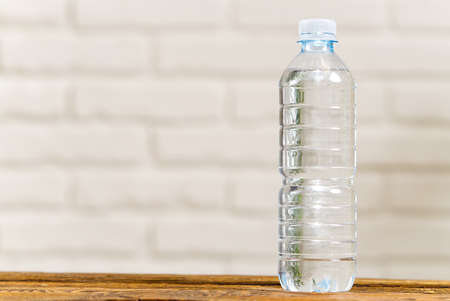 Drinking water in plastic bottle on wooden table and white wall. Health concept. clean water in transparent pet botlle, copy space