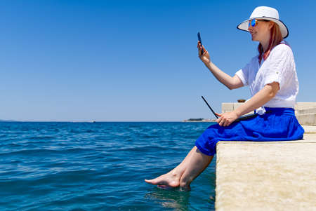 Work from anywhere. Side view of young woman, female freelancer in straw hat working on laptop while sitting on the beach. young woman in sitting on stone at sea and remotely working on laptop Banque d'images