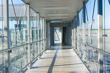 Passenger boarding bridge PBB to board airplane. Boarding gate entrance to train station from via skybridge. walking on jet bridge jetway, jetwalk, airgate, gangway, aerobridge, airbridge, skybridge