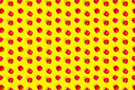 Bulgarian red ripe pepper on yellow backdrop. background from paprika, flat lay not seamless pattern