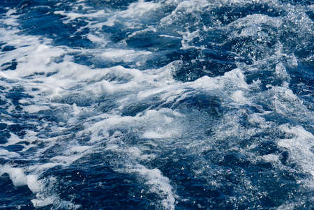 Rapid sea while sailing ship. deep turquoise and blue Mediterranean sea with texture background. Background shot of aqua sea water surface