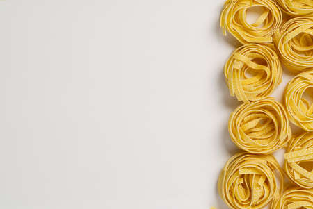 Fettuccine italian pasta isolated on white background. Raw tagliatelle nests isolated on white background. Traditional Italian pasta, flat lay copy space