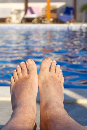 feet in front of blue water in open swimming pool in summer sunny day Banque d'images